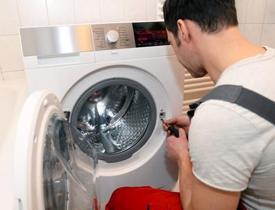 instalator naprawia pralkę